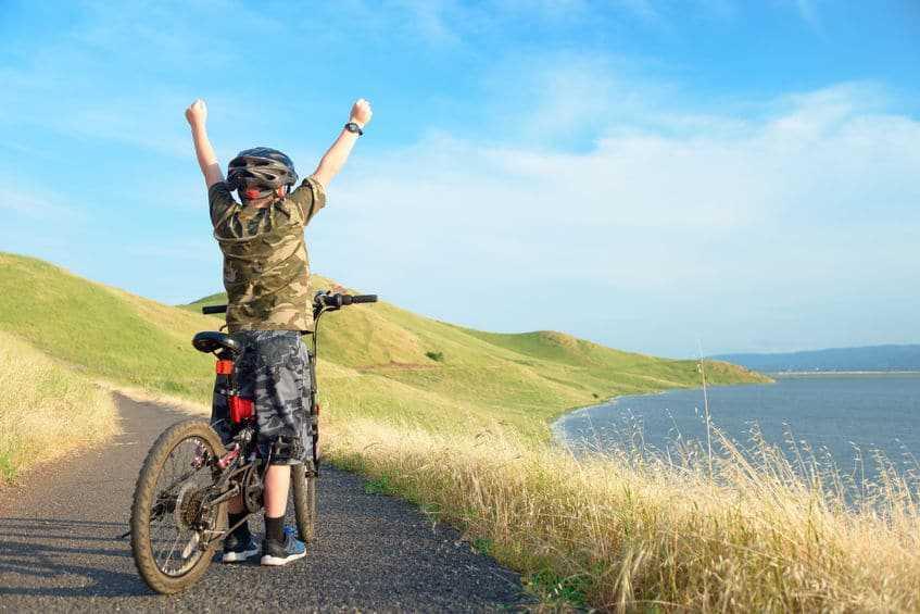 Fröhliches Kind bei einer Radreise mit den Eltern